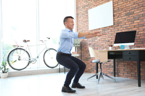 businessman-exercising-in-office