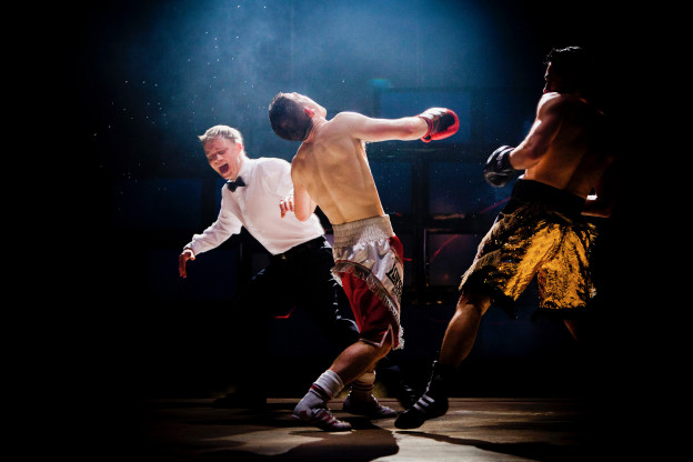 Wide shot of referee and two boxers in a ring; one has just punched the other who is reeling backwards