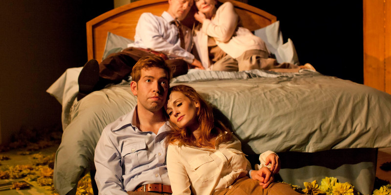An older couple are sat on a bed, leaning against the headboard; their heads together. A younger couple sit on the floor at the foot of the bed; her head on his shoulder