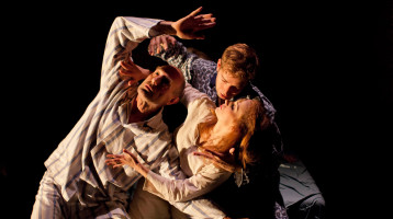 Two men and a woman in nightclothes are intertwined in dance.
