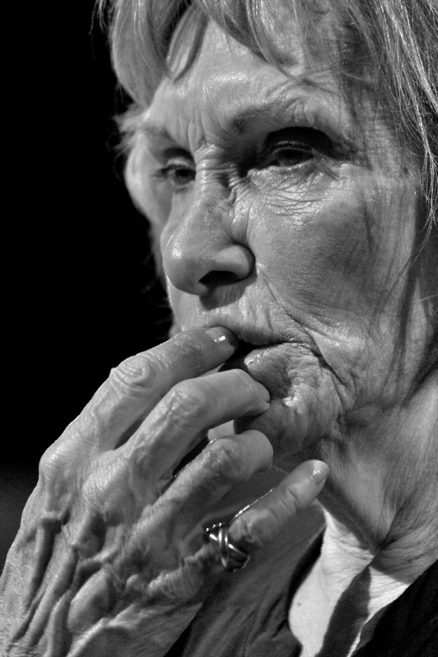 An older woamn has her hand to her mouth, wearing a worried expression