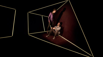 Performers - one standing, one sat on the floor – are held within the framework of an irregular three-dimensional shape