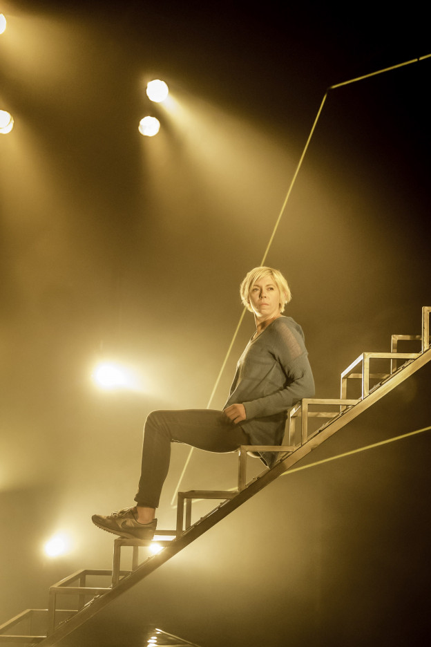 A woman sits on a metals framework staircase; it's not clear how high-up she is. Yellow spotlights casts light on and around her