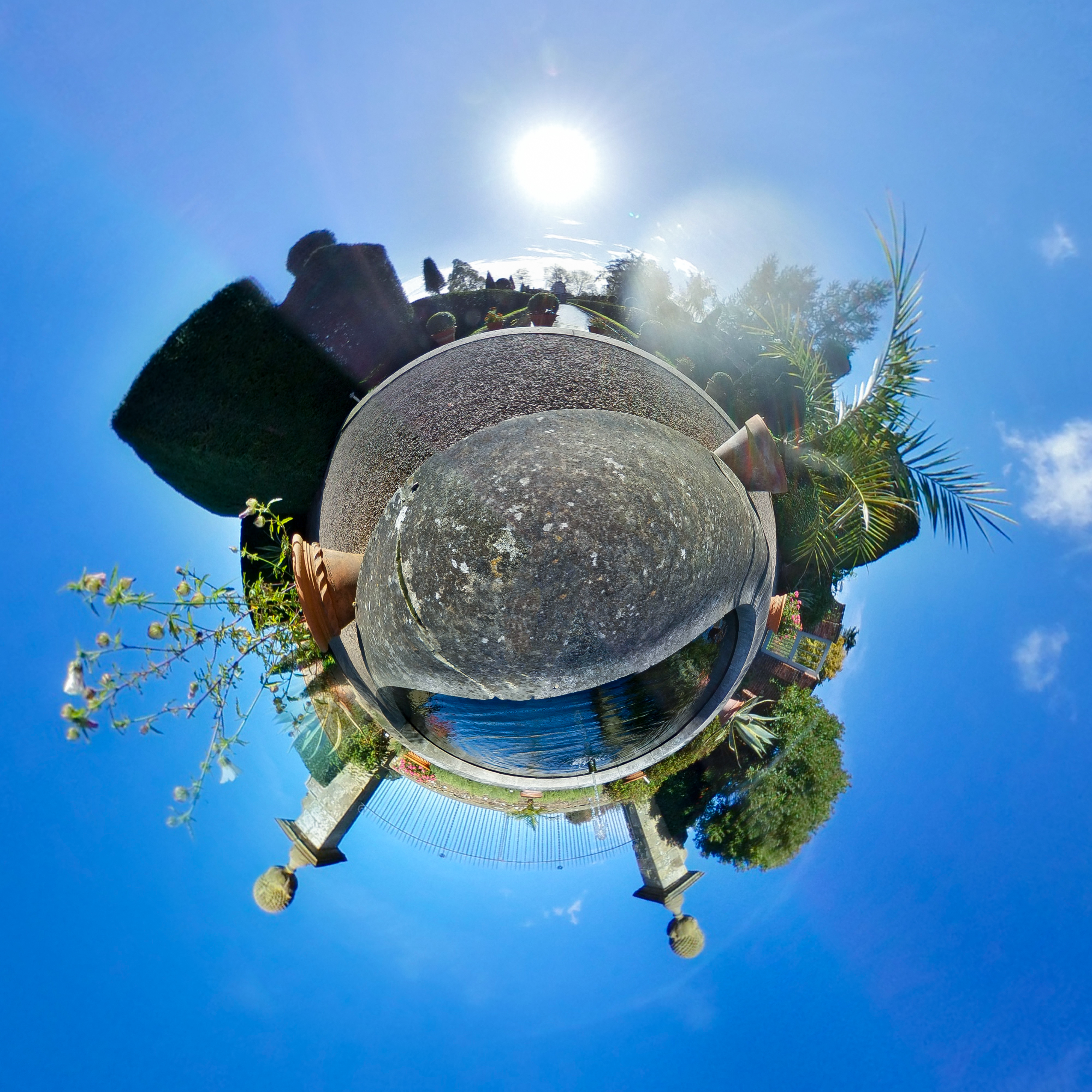 Distorted 360 photo of a classical water garden on a bright summer day, except the garden is circular and the fountain is upside down