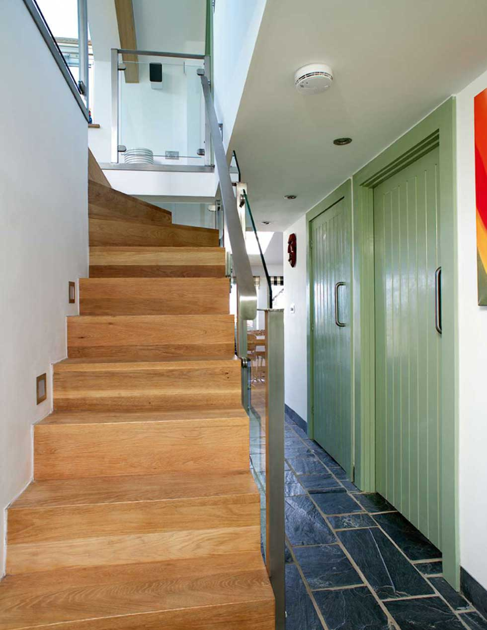 A wooden staircase with glass and steel balustrading