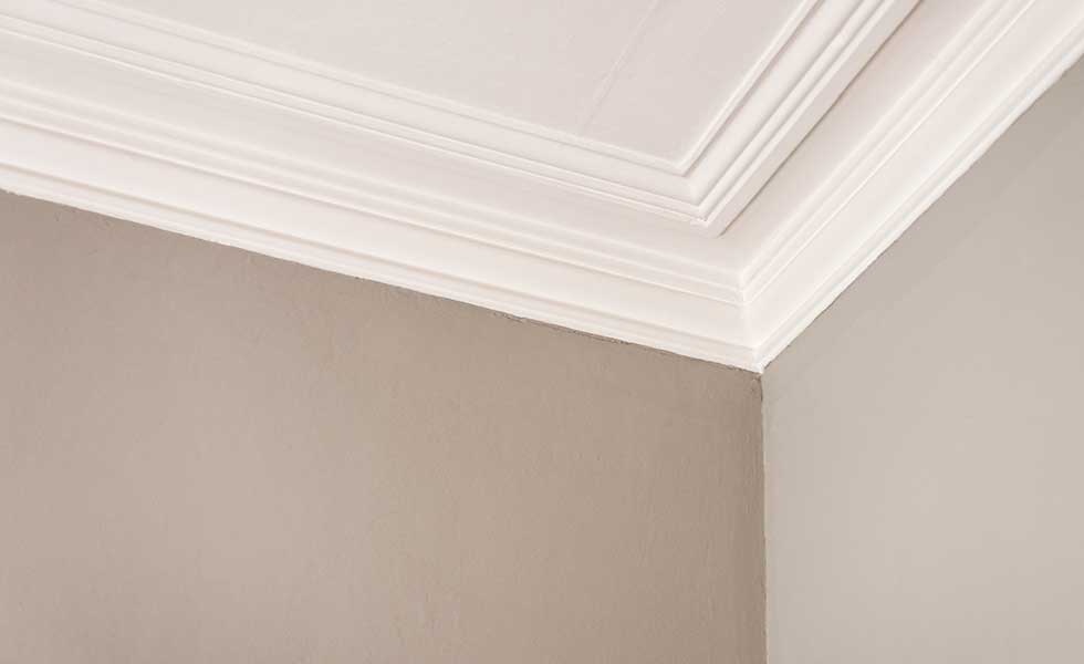 coving on a ceiling in a room with brown grey walls