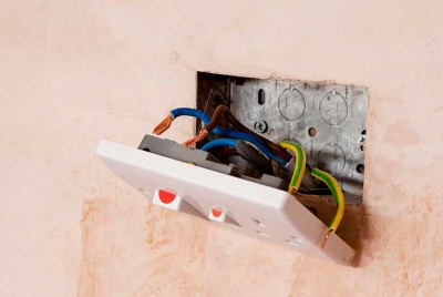 plug socket detached from a plastered wall