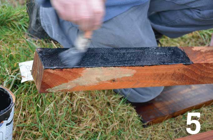 Brush on a couple of coats of bitumen-based paint on all sides and at the base of the post