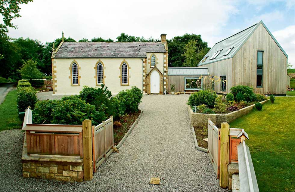 A converted stone church with a timber-clad extension