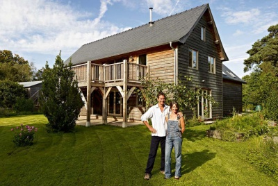 The Dawsons in front of their oak framed home