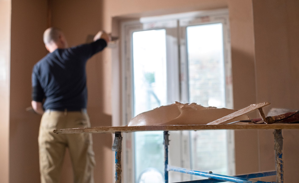 Man applying wet plaster to the wall