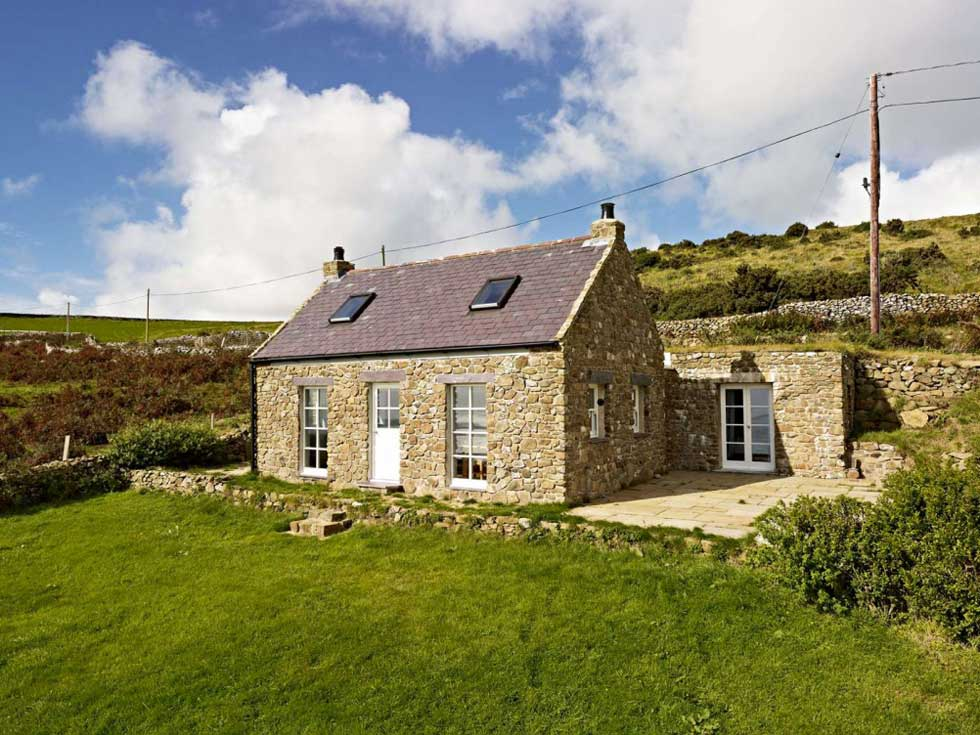 A tin shed converted into a stone cottage on the Welsh coast