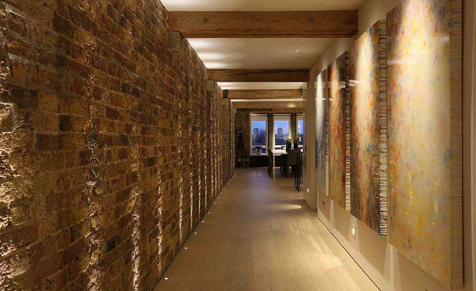Hallway with low ceilings and uplighters from John Cullen