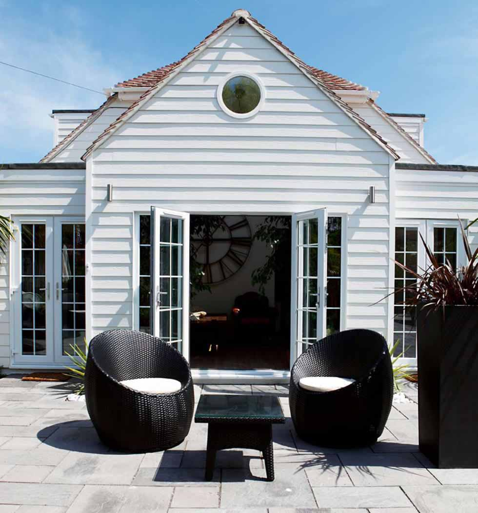 This 1960s renovation has been redesigned in a Cape Cod style with white weatherboard cladding