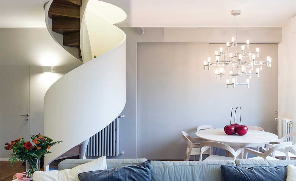 Contemporary spiral staircase with dramatic chandelier