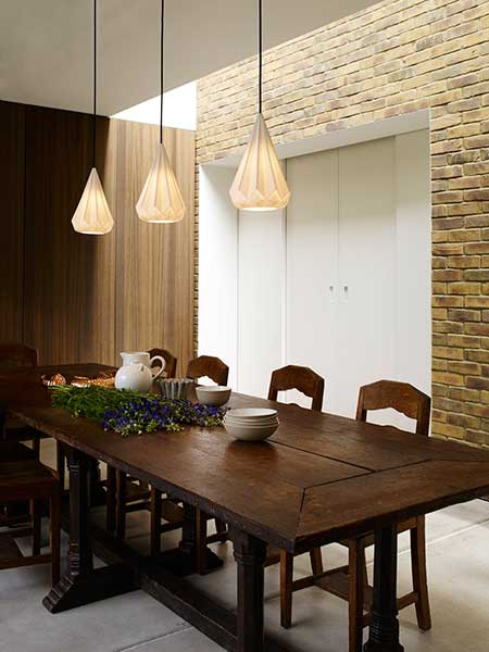 Long wooden dining table with pendant lighting