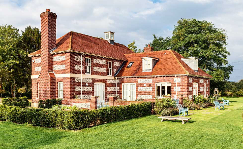 This brick and flint self build adopts Arts & Crafts techniques with its tall chimney and low roof pitch with dormer windows