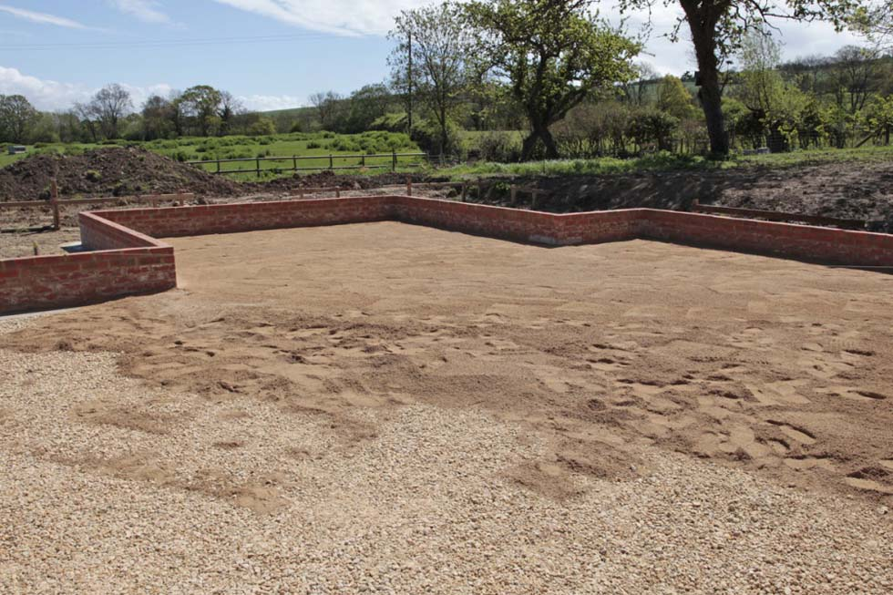 Coarse sand is added over the compacted stone