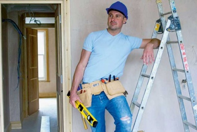 Man in hardhat leaning against step ladder