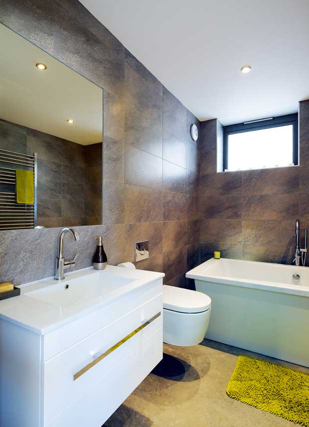 A contemporary bathroom with large, dark tiling