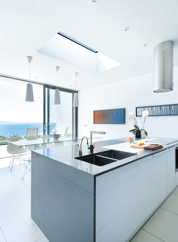The kitchen features a large island with induction hobs
