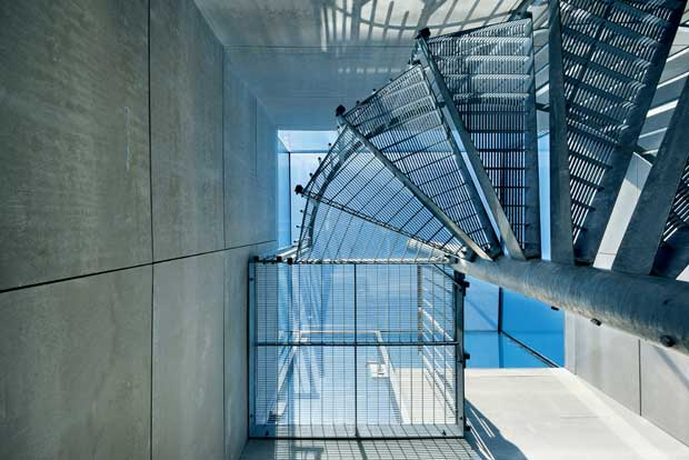 Industrial style spiral stairs serve as the main entrance