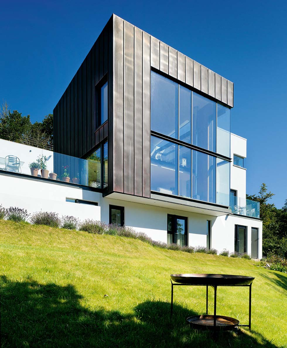 A glass and metal structure dominates the front of the house