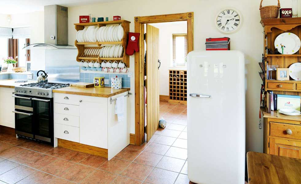 country style kitchen with plate rack and Smeg fridge freezer