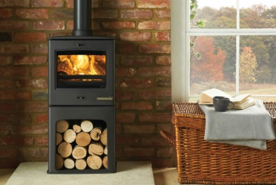 woodburning stove with logs underneath and exposed brick wall behind