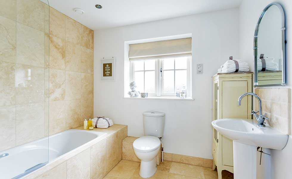 Travertine tiled bathroom with white suite