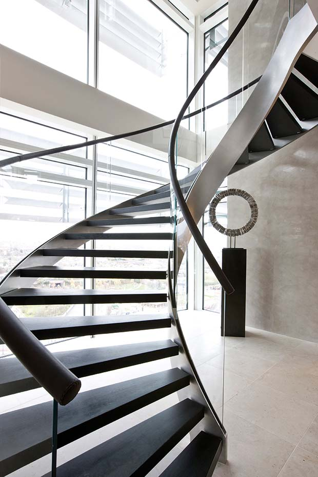 Helical staircase from Bisca with glass balustrades and brown leather handrail