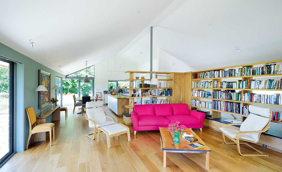 open plan living room with vaulted ceiling and bespoke bookshelves