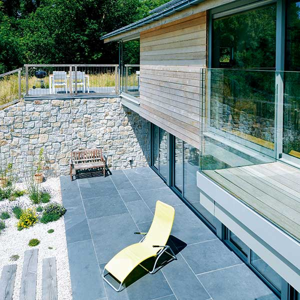 outdoor living space on a wood clad and granite stone home