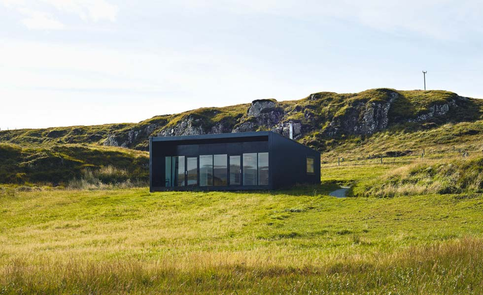 A low-profile lochside house designed to blend with its surroundings