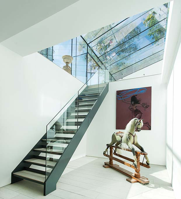 a frameless glass extension and staircase with glass balustrade and rocking horse