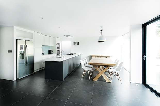 a matte white kitchen with large format grey floor tiles in an extension to a family home