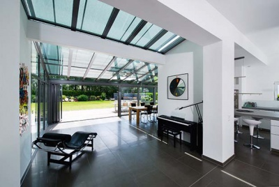 a sunroom with roof lights and folding sliding doors by Solarlux