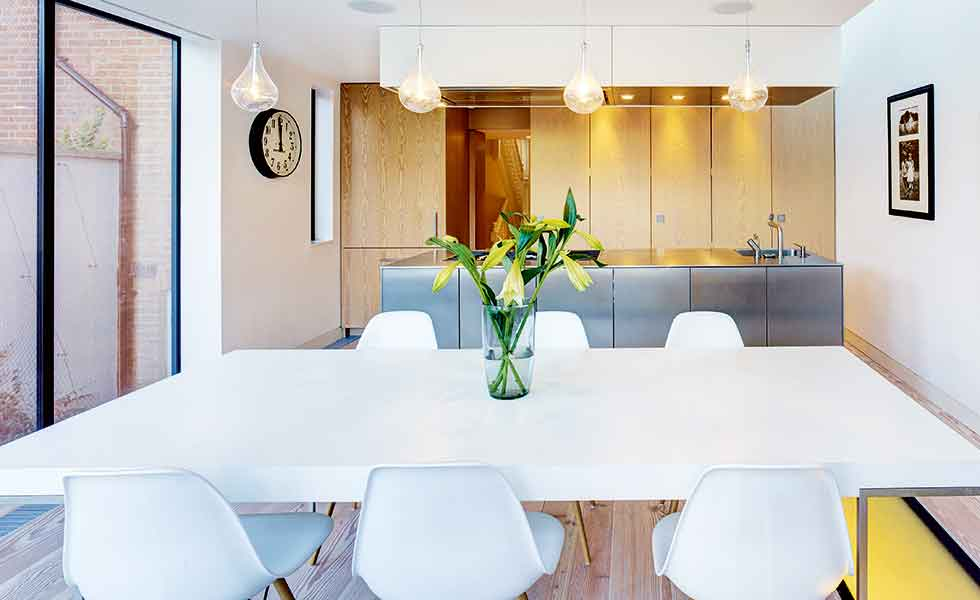 A kitchen diner in a modern extension with pendant lights