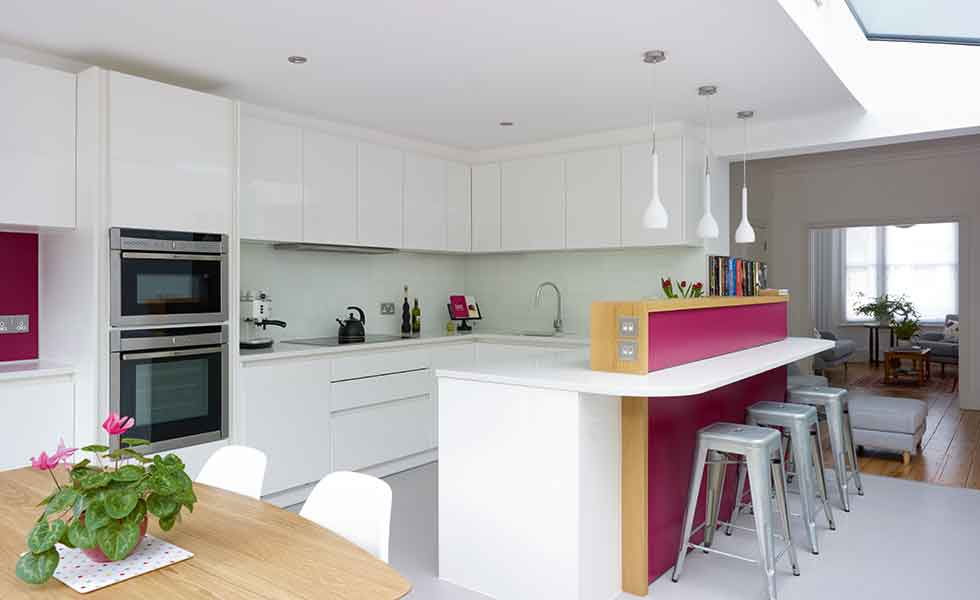 A side extension kitchen on a small terraced home with red feature low wall