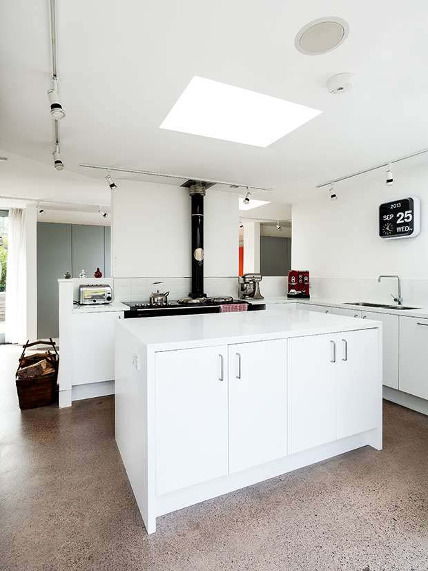 White Ikea units and Corian worktops create a sleek modern kitchen