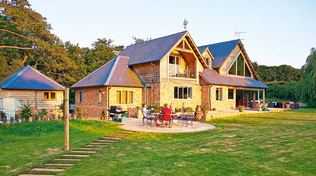 The rear elevation of an oak frame Isle of Wight home at sunset family outside