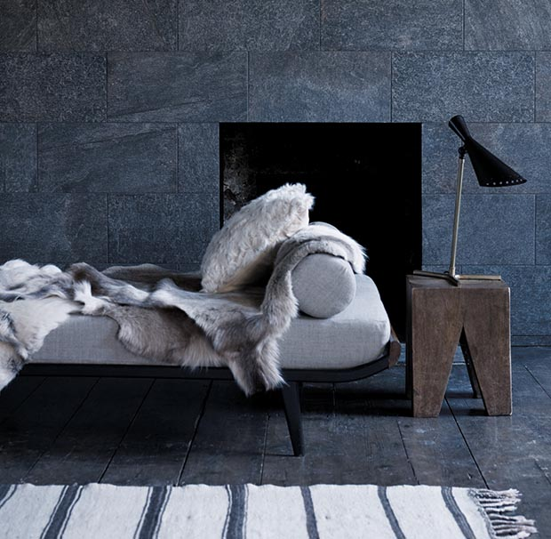 Fired Earth's Reykjavik large format dark grey tiles and a bed with reindeer pelt