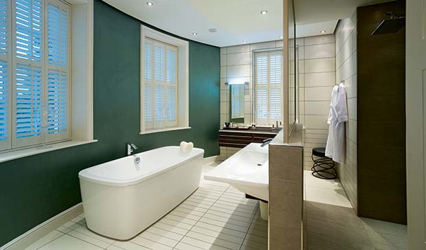 Sleek modern bathroom with teal walls and a room divide