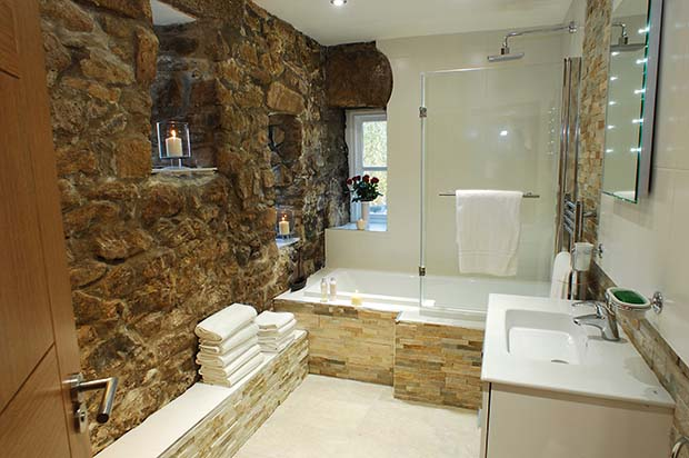 Exposed stone walls in a luxury bathroom in a barn conversion holiday let in Cornwall