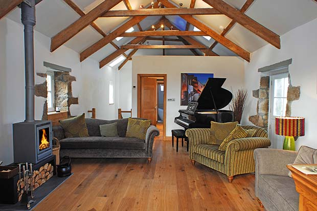 Grand piano and woodburning stove in a holiday barn in Padstow Cornwall