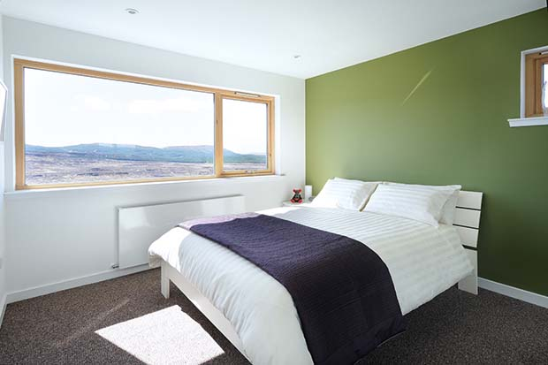 The bedroom of White Tail Croft with green wall and picture window