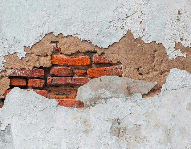 blown render on a white wall with exposed brickwork
