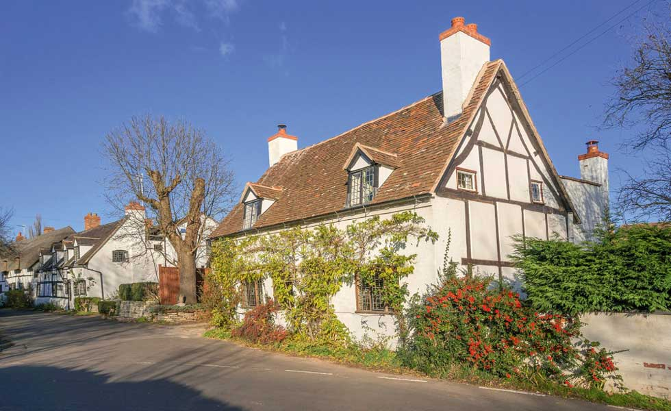 black and white timbered cottage in an English country village
