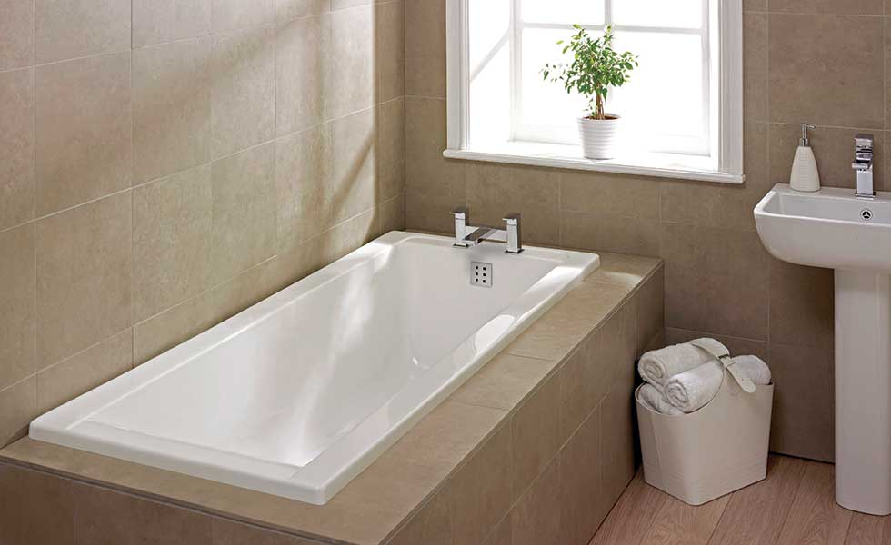 linear bath with pale wall tiles and surround