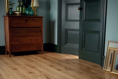 natural wood flooring in a dark room with blue-green paint